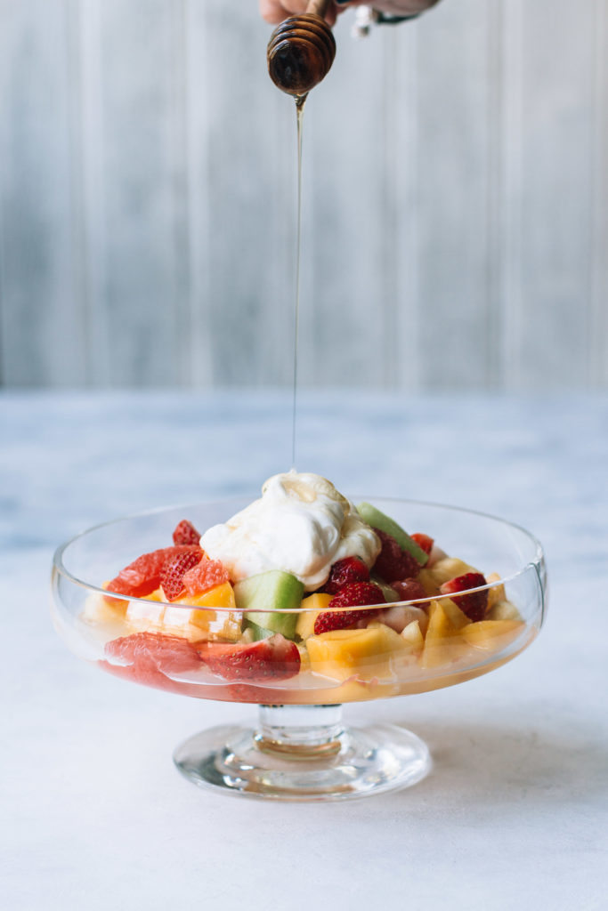 honey being drizzled over a bowl of yogurt and fruits